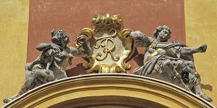 Königliches Signum und Steinskulpturen am Portal von Schloss Favorite Ludwigsburg.
